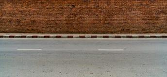 Alte Backsteinmauer mit konkretem Bürgersteig Stockbilder