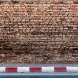 Alte Backsteinmauer mit konkretem Bürgersteig Stockfoto