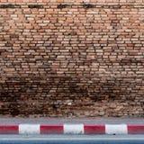 Alte Backsteinmauer mit konkretem Bürgersteig Lizenzfreie Stockfotos