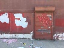 Alte Backsteinmauer mit metallischer Rollenfensterladentür Verlassenes Industriegebiet Stockfoto