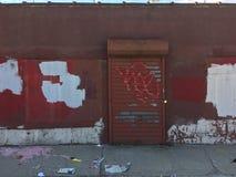 Alte Backsteinmauer mit metallischer Rollenfensterladentür Verlassenes Industriegebiet Lizenzfreie Stockbilder