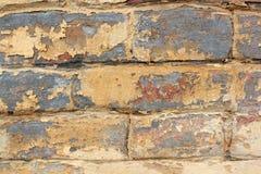Alte Backsteinmauer mit Resten der gelben und roten Farbe Lizenzfreie Stockbilder