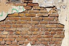 Alte Backsteinmauer mit Resten des Gipses Stockfotografie