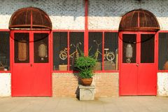 Alte Backsteinmauer mit roten Türen und Fenster und Blumentopf Stockfotografie