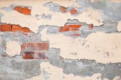 Alte Backsteinmauer mit schädigendem Stuck und gelber Farbe Stockbilder