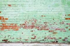 Alte Backsteinmauer mit schädigender Schicht grüner Farbe Stockfotos