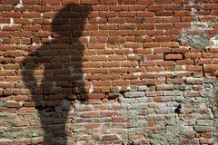 Alte Backsteinmauer mit Schatten des Revolverheldes Stockbild