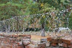 Alte Backsteinmauer mit Stacheldraht Lizenzfreie Stockfotografie