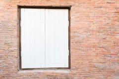 Alte Backsteinmauer mit weißem Fenster Lizenzfreies Stockfoto