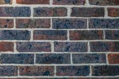 Alte Backsteinmauer mit weißen Zeige-, roten und purpurroten Ziegelsteinen Lizenzfreies Stockbild