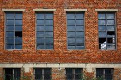 Alte Backsteinmauer mit zerbrochenen Fensterscheiben Lizenzfreie Stockfotos