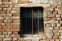 Alte Backsteinmauer mit Ziegelstein füllte Fenster mit Gitter Lizenzfreie Stockfotografie