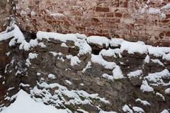 Alte Backsteinmauer und die Grundlage eines Hauses im Schnee Stockfotos