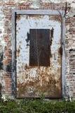 Alte Backsteinmauer und eine rostige Metalltür Lizenzfreies Stockfoto