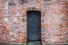 Alte Backsteinmauer- und Schmiedeeisentür des Hintergrundes Stockfotos
