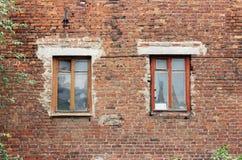 Alte Backsteinmauer und zwei Fenster in einem Hintergrund Stockbild