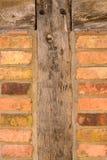Alte Backsteinmauerbeschaffenheit mit hölzernen Senkrechten Lizenzfreie Stockfotografie