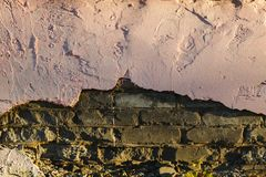 Alte Backsteinmauerbeschaffenheit unter großem unterem großem Stück Gips Co Lizenzfreie Stockfotografie