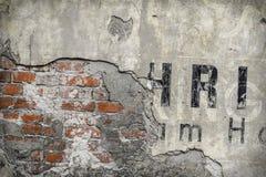 Alte Backsteinmauermusternahaufnahme mit Fragmenten von Buchstaben Stockfotografie