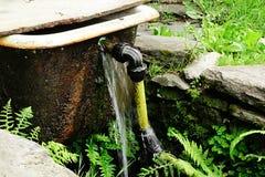 Alte Badewanne mit dem gelben Rohr, das als Sperre installiert ist und Wasserreservoir auf Wald strömen Lizenzfreie Stockbilder
