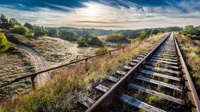 Alte Bahnlinie am eisigen Morgen über dem Wald Stockfotografie