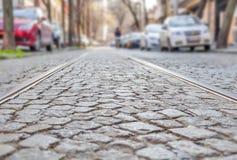 Alte Bahnstrecken auf cobbled Straßendecke Lizenzfreie Stockfotos