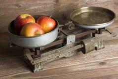 Alte Balance mit Äpfeln Lizenzfreie Stockbilder