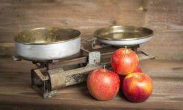 Alte Balance mit Äpfeln Stockbilder