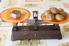 Alte Balancenskala mit zwei Wannen mit Kiwis Stockfotos