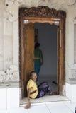 Alte Balinesefrau, die in der Tür sitzt Stockbild