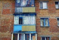 Alte Balkone mit Fenstern auf der Backsteinmauer des Hauses Lizenzfreies Stockfoto