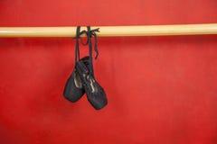 Alte Ballett-Schuhe, die vom Barre hängen Lizenzfreies Stockbild