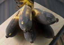 Alte Bananen-Frucht auf einem hölzernen Brett Stockbild