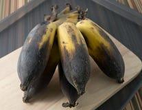 Alte Bananen-Frucht auf einem hölzernen Brett Lizenzfreie Stockbilder
