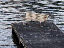 Alte Bank auf einem Dock im Wasser Lizenzfreies Stockfoto