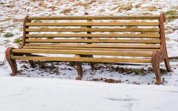 Alte Bank auf Hintergründen eines Schneewinters Stockfoto