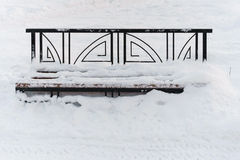Alte Bank auf Hintergründen eines Schneewinters Stockbild