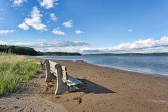 Alte Bank auf Strand mit Fluss im Hintergrund Lizenzfreie Stockfotografie