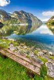 Alte Bank am Gebirgssee in den Alpen Lizenzfreies Stockfoto