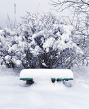 Alte Bank im Garten nachdem dem Schneien Lizenzfreies Stockbild