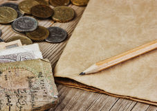 Alte Banknoten und Münzen und Bleistift Stockfotografie