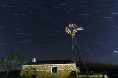 Alte Bauernhof-Windmühle für pumpendes Wasser mit spinnenden Blättern Stockfotos