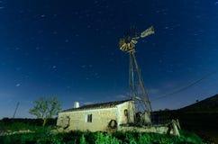 Alte Bauernhof-Windmühle für pumpendes Wasser mit spinnenden Blättern Stockbilder