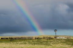 Alte Bauernhof-Windmühle und Regenbogen Stockbild