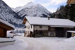 Alte Bauernhofwinterlandschaft und -berge Lizenzfreies Stockfoto
