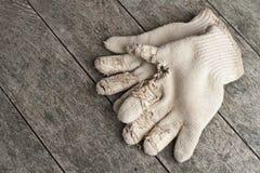 Alte Baumwollarbeitshandschuhe auf verwittertem Holz. Stockfotos