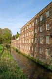 Alte Baumwollspinnerei neben Fluss Stockbilder