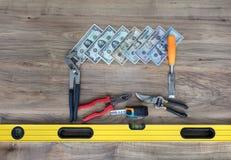 Alte Bauwerkzeuge und ein Satz Dollarscheine auf einer Holztischnahaufnahme Stockfotografie