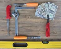 Alte Bauwerkzeuge und ein Satz Dollarscheine auf einer Holztischnahaufnahme Stockfoto