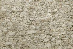 Alte beige Steinwand-Hintergrundbeschaffenheit Stockfotos